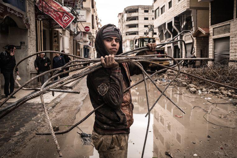 Een jongen werkt in een verwoest Gaza.  Beeld Zolin Nicola
