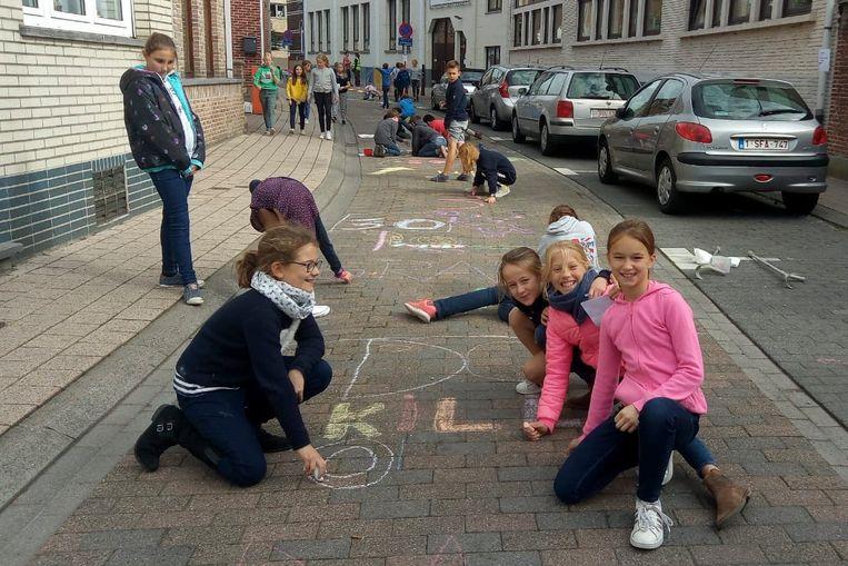 De leerlingen van het vijfde leerjaar van de Vrije Sint-Clemensschool in Hoeilaart voeren actie aan hun schoolpoort voor een zone 30.