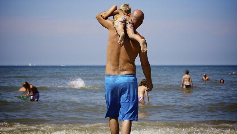 Een vader loopt met zijn zoon naar de zee. Beeld anp
