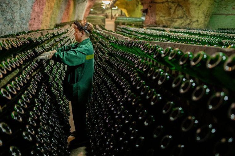 Ruim dertien miljoen flessen liggen er opgeslagen. Om de vijftien dagen worden de 'rijpende' flessen een kwartslag gedraaid.  Beeld Emile Ducke