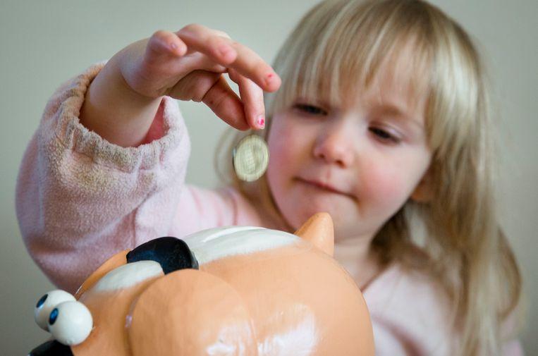 Een meisje stopt geld in haar spaarpot. Beeld ANP XTRA