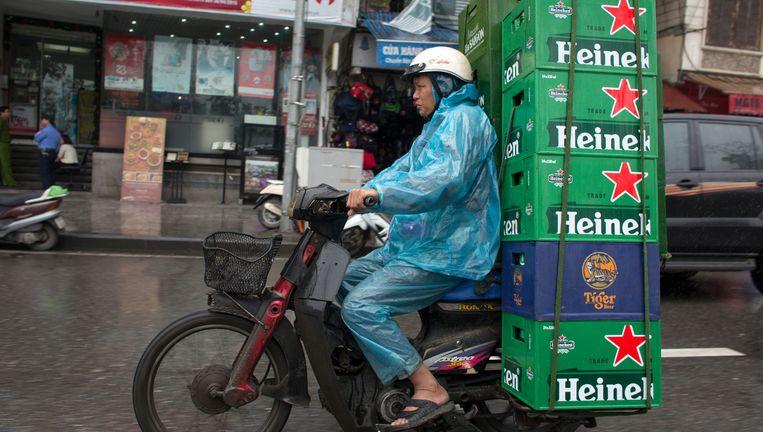 Een bezorgscooter bepakt met bier in Vietnam, waar Heineken een sterke positie heeft. Elders in de wereld dreigt de Nederlandse brouwer te worden overschaduwd door het nieuwe fusiebedrijf. Beeld Frank Schall