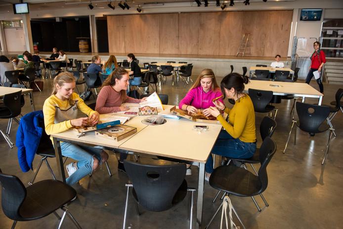 Leerlingen van het OLV in Breda moeten  wachten door de stakingen van de leraren. Een paar kleine groepjes zitten te wachten op hun vervolglessen, tussentijds hebben ze een pizza gehaald. Want ook de catering is dicht vandaag