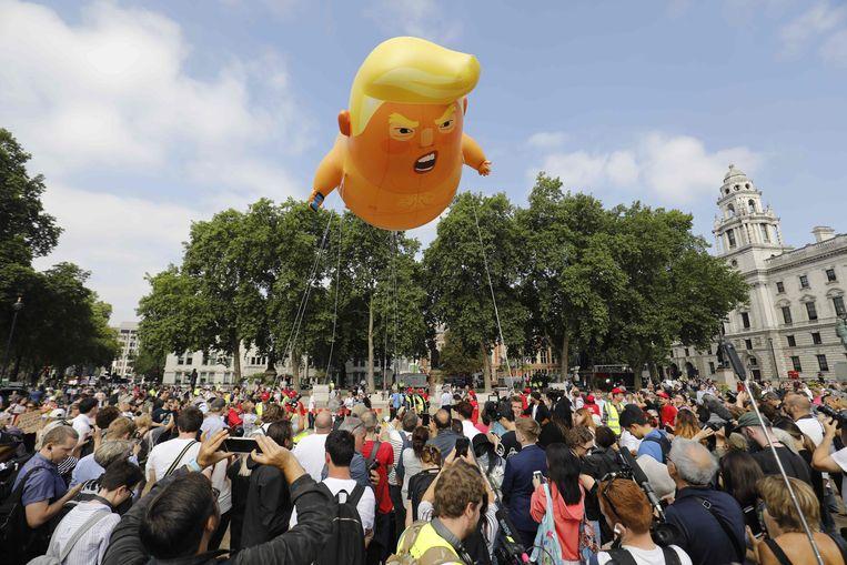 Tijdens een protest tegen Trump in Londen werd vandaag een luchtballon opgelaten die de president voorstelde als baby.  Beeld AFP