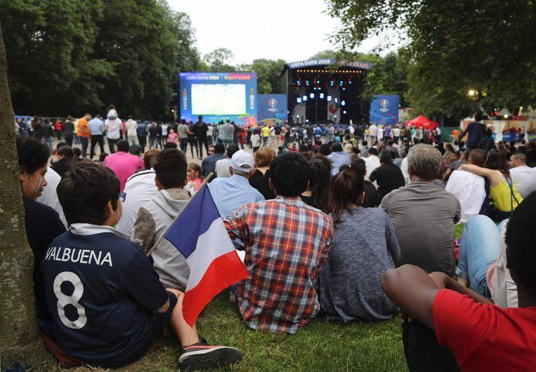 Supporters zitten in de fanzone in Saint-Denis, Parijs bij het begin van de wedstrijd tussen Frankrijk en Roemenië. Beeld afp