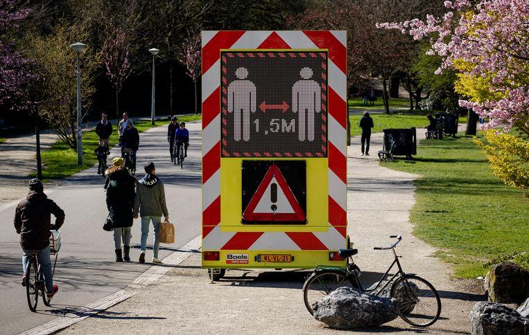 Een bord waarschuwt om 1,5 meter afstand te houden van elkaar. Beeld ANP
