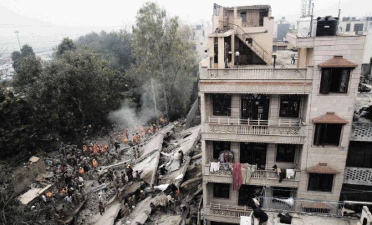 Reddingswerkers zoeken in de puinhopen van de ingestorte flat in Delhi naar overlevenden. (FOTO REUTERS ) Beeld REUTERS