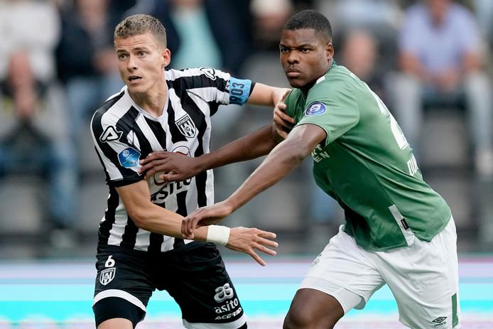 Dario van den Buijs (links) vecht een verbeten duel uit met  Denzel Dumfries van PSV.