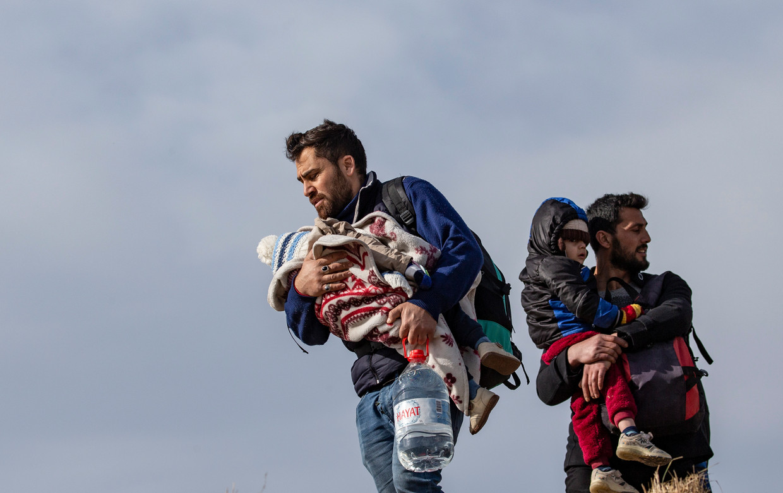 Vaders met hun kinderen proberen bij het West-Turkse Edirne de grens met Griekenland over te steken, begin maart dit jaar. Beeld Erdem Sahin / EPA