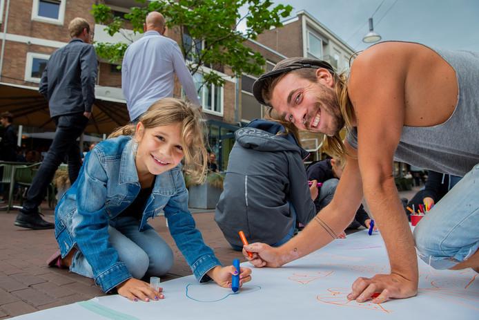 Kunstenaars dagen bezoekers van de Nijmeegse binnenstad uit om te tekenen, hier in de Lange Hezelstraat.