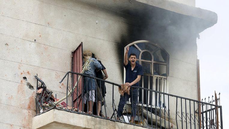 Een man bij zijn huis in Sanaa dat werd geraakt door een luchtaanval. Beeld reuters