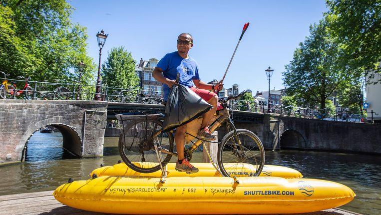 Milieuactivist Dhruv Boruah vist op zijn waterfiets plastic uit de grachten. Beeld Dingena Mol