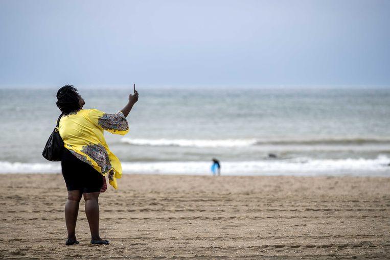 Een strandgangster trotseert de wind op het strand van Scheveningen. Er komt een zomerstorm, met mogelijk windkracht 9 aan de kust.  Beeld ANP