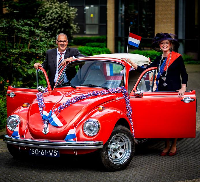 Burgemeester Reinie Melissant-Briene en haar man op weg in een Volkswagen cabrio naar mensen om hen persoonlijk uit te nodigen voor een lintje.