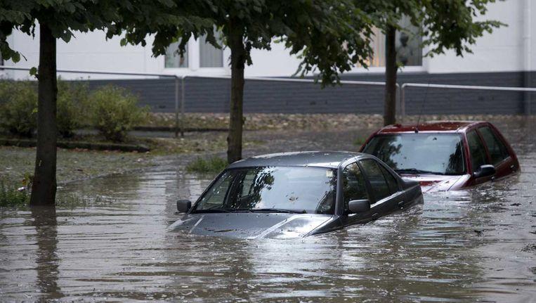 Auto's staan op 3 augustus onder water in Meerssen. Beeld anp