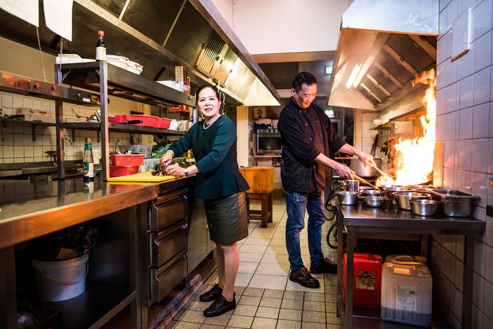 Actie in de keuken bij Memories of Asia. Eigenaresse Zen Hua Lin snijdt de groenten,  chefkok Kim Poh Tong flambeert een gerecht.