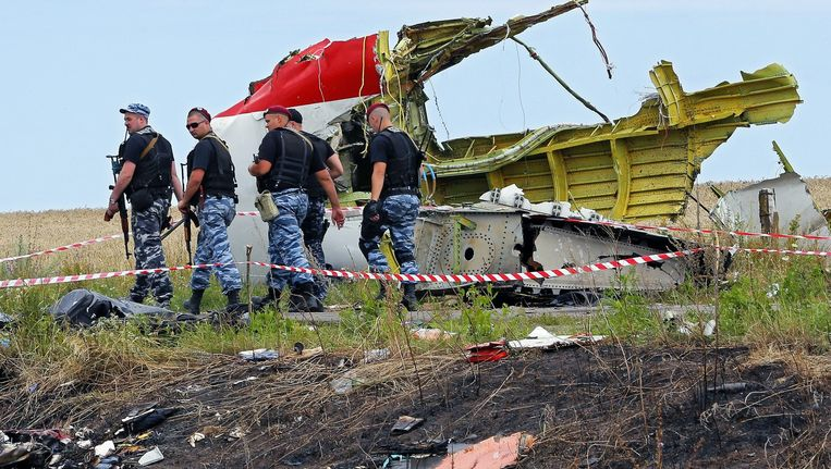 Gewapende rebellen lopen langs brokstukken van het neergestorte vliegtuig. Beeld epa