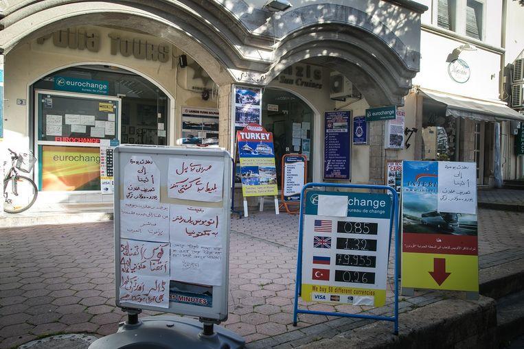 Op een reclamebord voor de deur van Kos Travels wordt de busreis naar de grens met Macedonië in het Arabisch aangeprezen. Beeld null