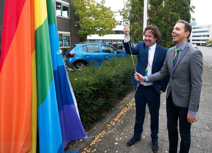 Simon Timmerman van het COC Midden Nederland (r) en wethouder George Becht hijsen de regenboogvlag bij het stadhuis in Woerden.