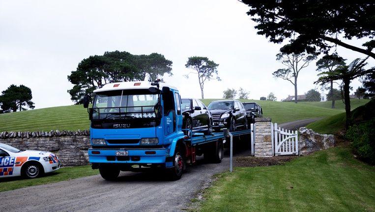 Tijdens de politie-inval op zijn landgoed boven Auckland, eind januari, worden in beslag genomen auto's van internetondernemer Kim Dotcom weggevoerd. Beeld getty