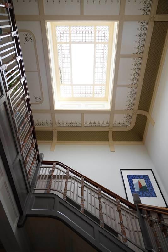 De trappenhal met lichtkoepel in glas-in-lood.
