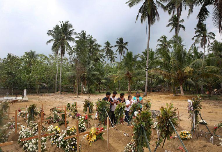 Nabestaanden van slachtoffers van de aanslagen op Sri Lanka bidden op het kerkhof. Meer dan 250 mensen kwamen vorige week om het leven bij door IS geclaimde terreur.