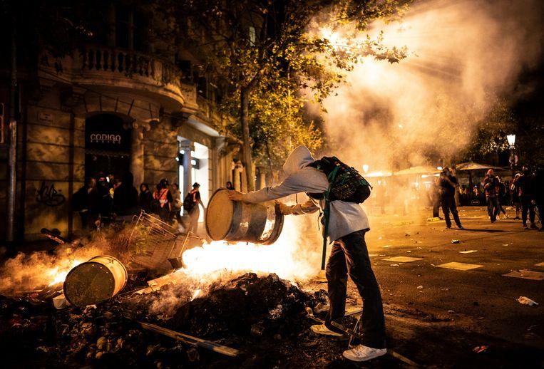 Een man gooit een ton op een door de portesterende Catalanen aangestoken vuur op rambla de Catalunya in Barcelona.  Beeld Freek van den Bergh / de Volkskrant