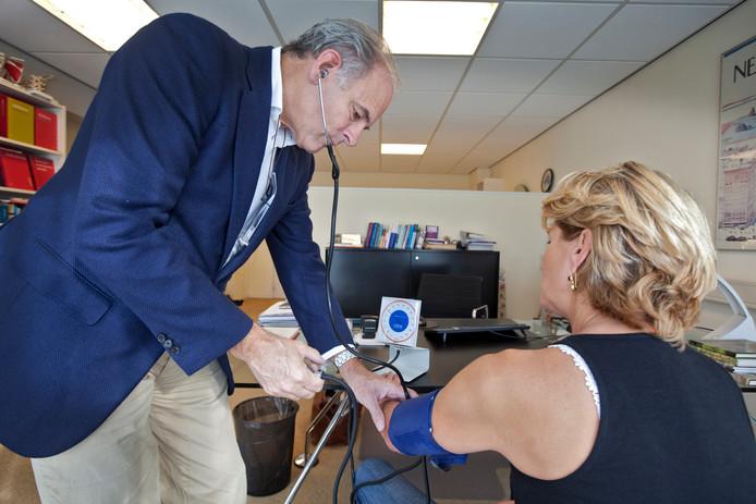 Een patiënt laat bij de huisarts laat bloeddruk meten. foto ANP