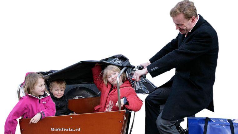 Een trotse bakfietsvader haalt zijn kinderen van school. Beeld Bert Verhoeff