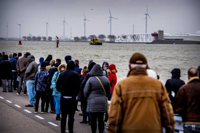 Mensen staan bij de Maeslantkering in afwachting van de mogelijke sluiting.