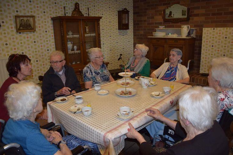 Bewoners van Sint-Anna zitten gezellig rond de tafel in de kamer 'uit de tijd van toen'.