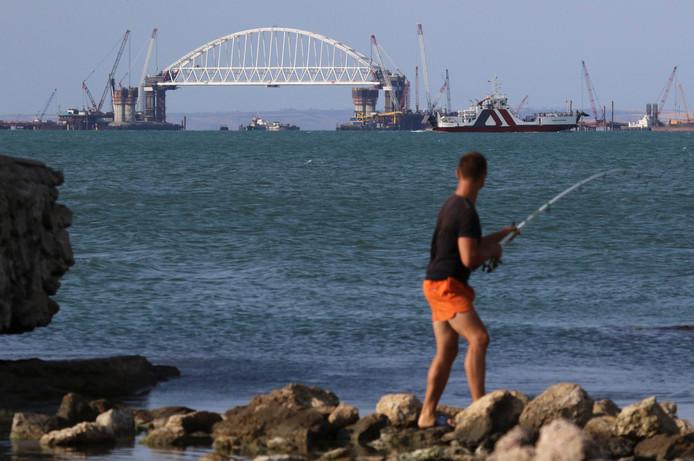 Een visser ziet de bouw van de Krimbrug voor zich.