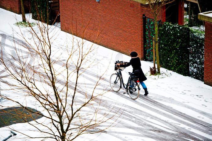 Een vrouw loopt met de fiets aan de hand. De sneeuw zorgt niet alleen voor pret, maar ook voor overlast in het verkeer. Weggebruikers krijgen te maken met gladheid door sneeuw en ijzel.
