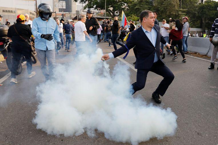Een opponent van president Maduro gooit met traangas in de buurt van luchtmachtbasis La Carlota.