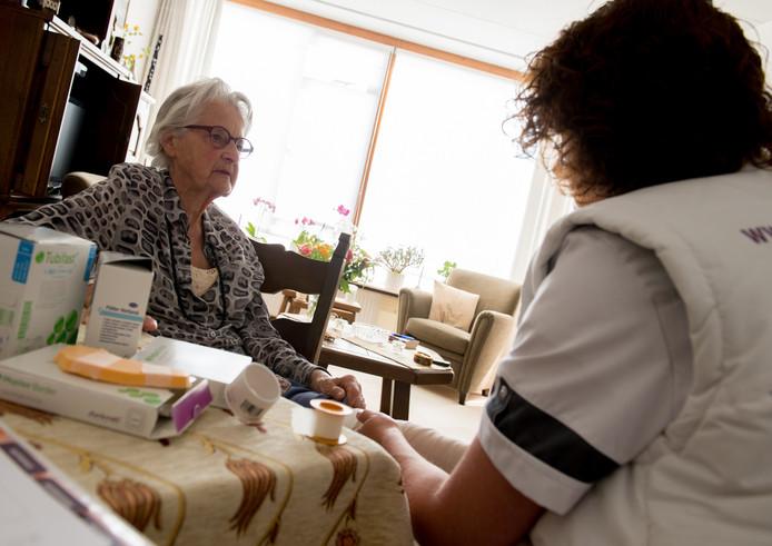 Een verpleegkundige van de thuiszorg verzorgt een van haar klanten.