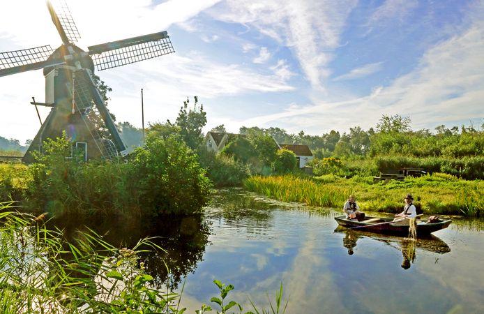 Ecologen Nortbert Daemen en Roelf Pot aan boord van hun sloepje, in de schaduw van de molen De Trouwe Wachter in Tienhoven.