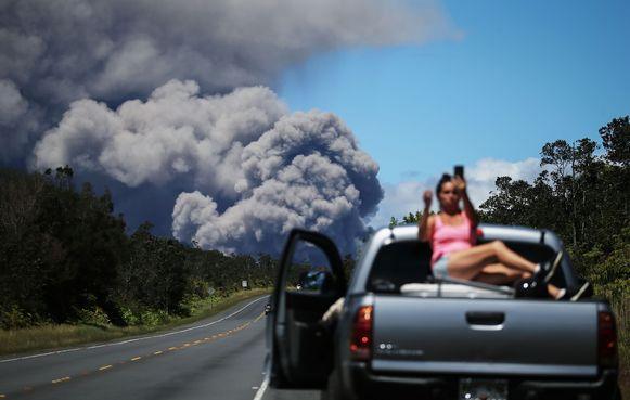 Een vrouw neemt een selfie met op de achtergrond de mogelijk giftige aswolk.