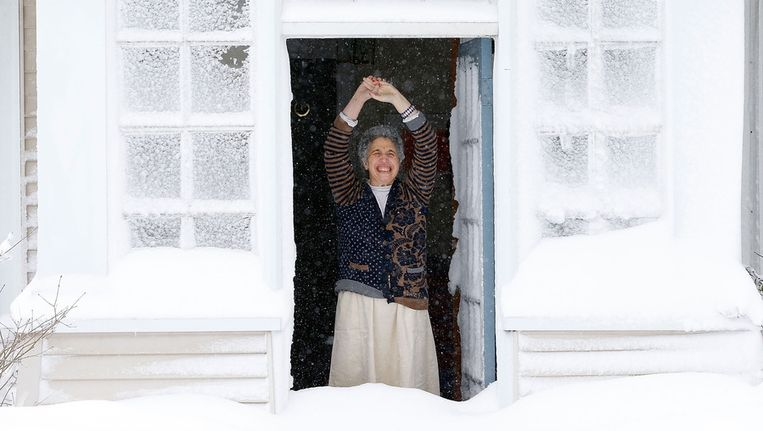 Een vrouw maakt haar voordeur open en ziet hoe hoog de sneeuw ligt. Beeld getty