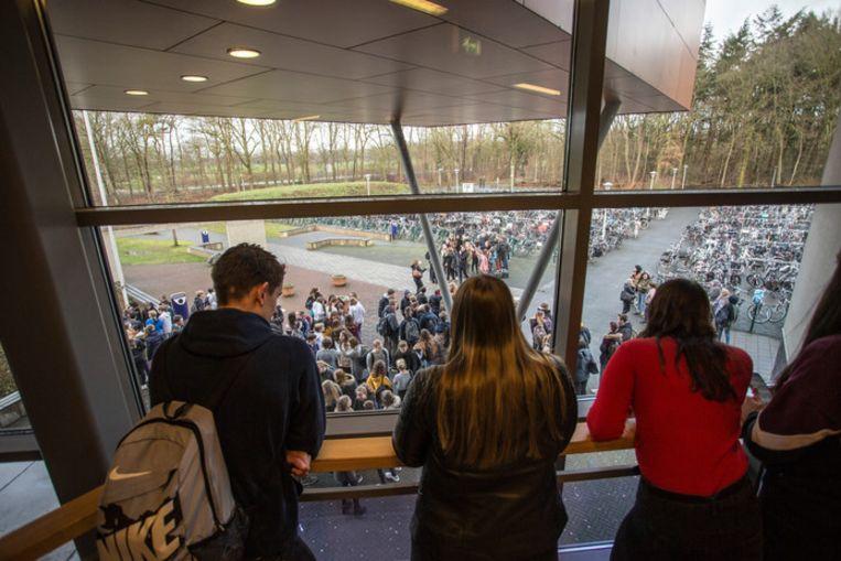 Medescholieren kijken naar de demonstratie vanuit de school.