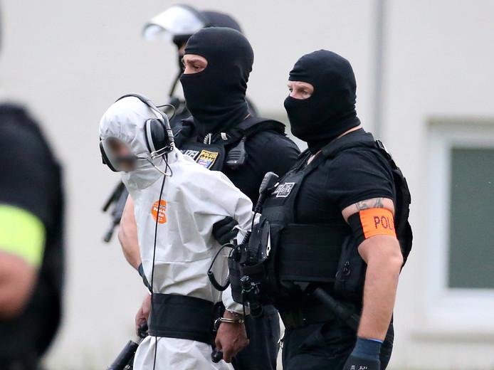 Leden van een speciale politie-eenheid begeleiden Ali Bashar na zijn verhoor door het OM in Wiesbaden naar een helikopter die hem terugvliegt naar de gevangenis.
