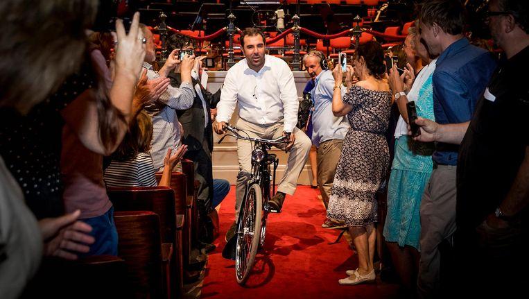 De Italiaan Daniele Gatti neemt een fiets in ontvangst bij zijn aanstelling als chef-dirigent Beeld ANP