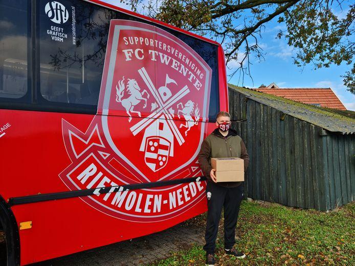 Een lid van FC Twente-Rietmolen-Neede met een matchdaypakket voor de supportersbus van de vereniging.