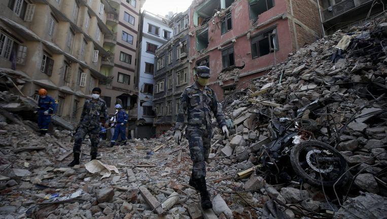 Nepalese militairen en hulpdiensten lopen tussen de ravage in Balaju, Kathmandu, aangericht door de grote aardbeving die het land trof op 25 april, 2015. Beeld epa
