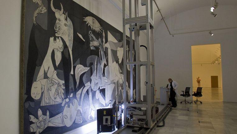 Een technicus werkt aan Pablo Picasso's 'Guernica' schilderij in het Reina Sofia Museum in Madrid. Beeld ap