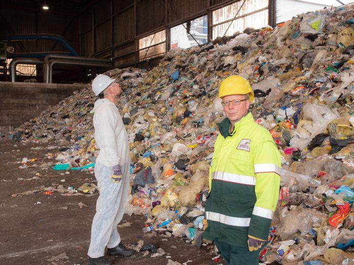 Robert Corijn van Attero (voorgrond) en verslaggever Joost Dijkgraaf bij een enorme stapel plastic afval uit Twente.