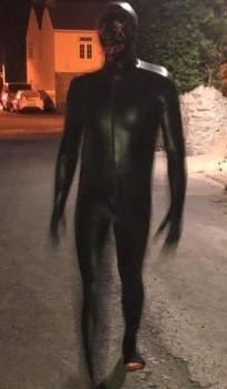 De man is gehuld in een rubberen sm-outfit.
