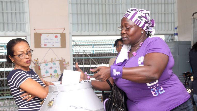 Een aanhanger van de NDP van Desi Bouterse brengt haar stem uit in Paramaribo. Om 12.00 Nederlandse tijd gingen de stembussen open. Beeld afp