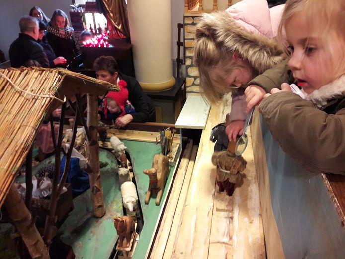 Kinderen kijken naar de bewegende kerststal in Koolwijk.