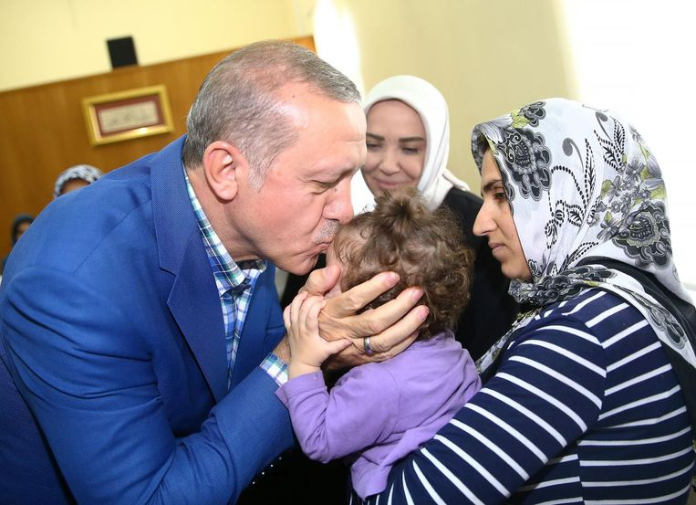 De Turkse president Erdogan kust een kind bij een bijeenkomst voor families van slachtoffers na de aanslag in Diyarbakir. Beeld afp