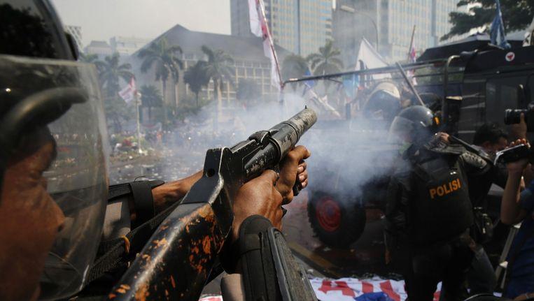 Een agent vuurt traangas af op betogers. Beeld null
